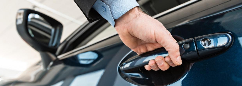 Man doet pakt portier van auto vast
