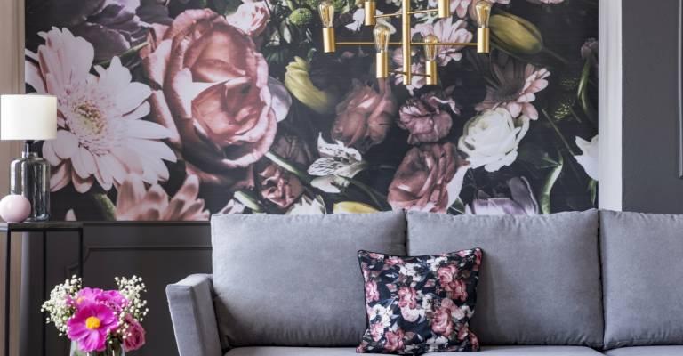 Fotobehang met bloemen achter grijze bank